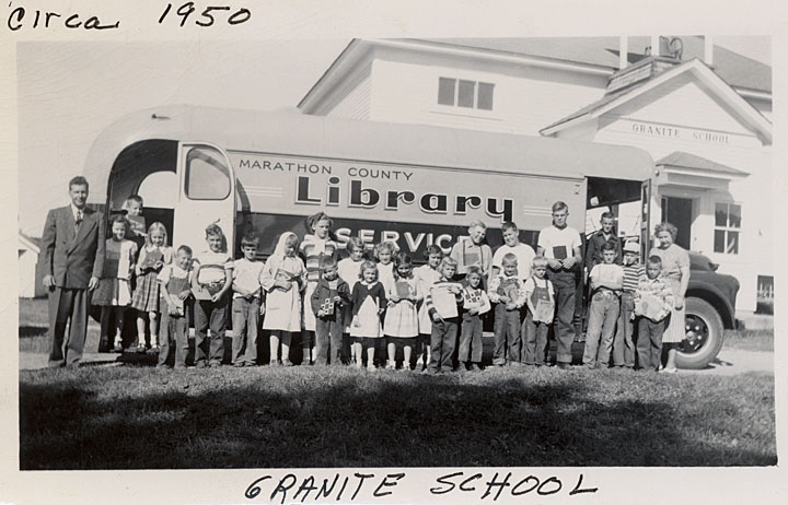 Black and white image of children in front of a bookmobile