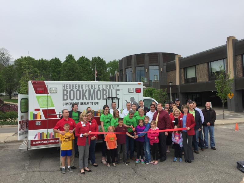 Photo of community members standing in front of bookmobile for ribbon cutting ceremony