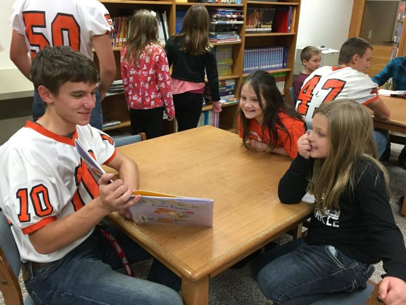 Varsity football player reads to 2 fourth graders