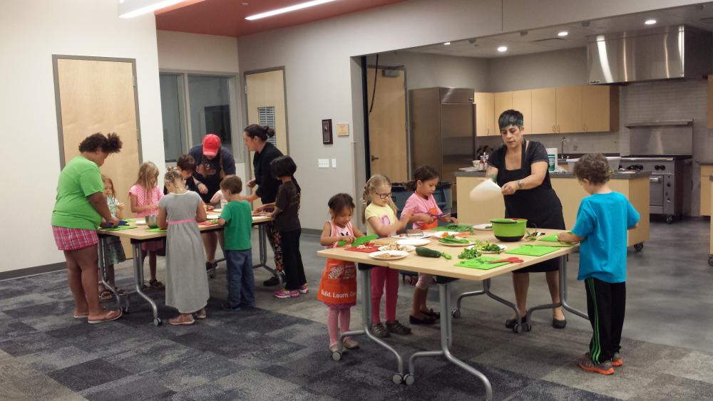 Kids participate in a cooking class featuring fresh fruits  and vegetables at Meadowridge Library
