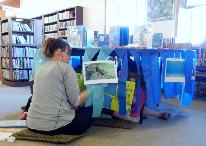 Kids are read stories while sitting under a table with blue streamers to simulate the being in the deepest part of the ocean