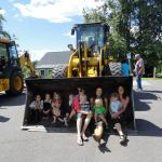 Children and adults sitting in the bucket of a loader truck