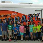 Kids standing in front of the bookmobile
